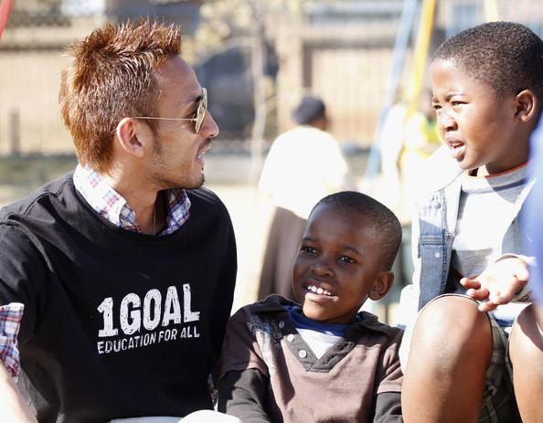 Hidetoshi Nakata in compagnia di due bimbi africani