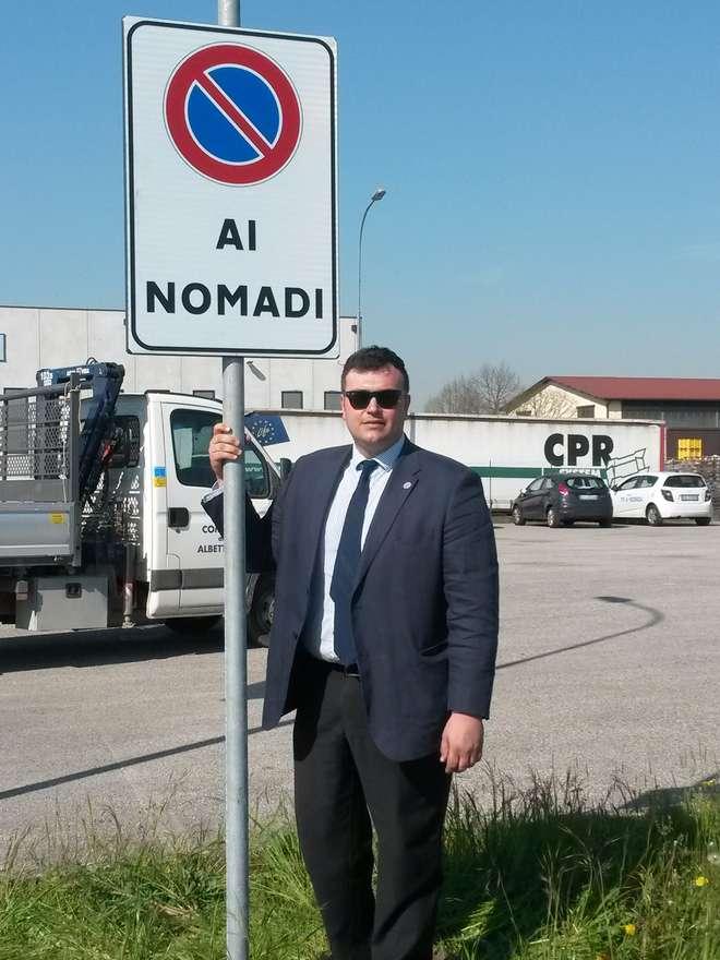 Joe Formaggio posa accanto al cartello anti-nomadi